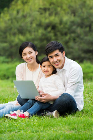 Happy family using laptop on the grass