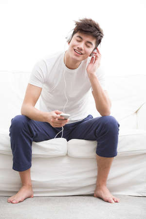 Young man listening to music on smart phone