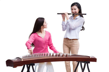 indian style sitting: Young women playing traditional Chinese musical instruments