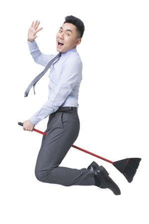 Young businessman flying on broom LANG_EVOIMAGES