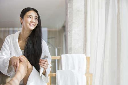 oriental bathrobe: Young woman applying moisturizer to leg LANG_EVOIMAGES