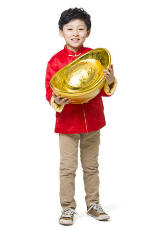 Happy boy holding a large Chinese traditional currency yuanbao LANG_EVOIMAGES