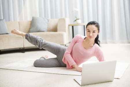 self conscious: Young woman practicing yoga with laptop in living room