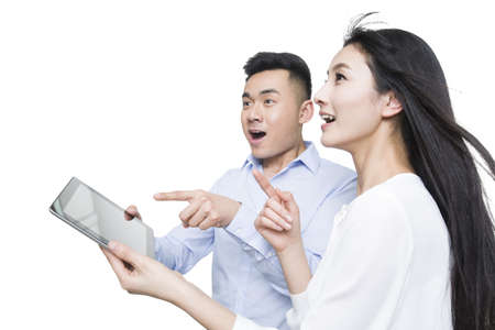 Young couple holding digital tablet with surprised expression