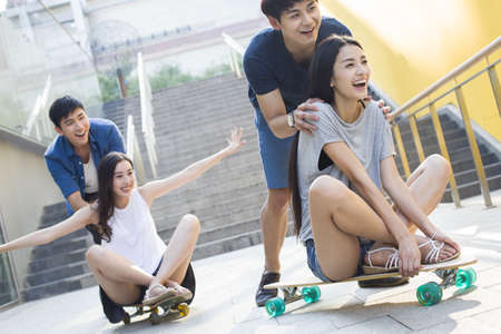 staircases: Young men pushing girlfriends on skateboards