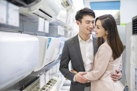 major household appliance: Young couple buying air conditioner in electronics store