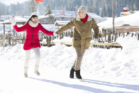 chainlink fence: Young couple holding hands running in the snow