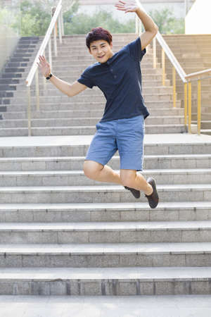 staircases: Young man jumping down steps LANG_EVOIMAGES