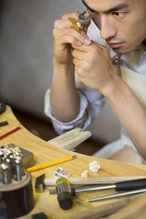 Male jeweler examining a diamond with loupe