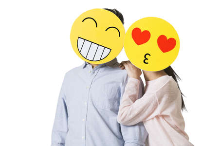 Young couple with cartoon emoticon faces in front of their faces
