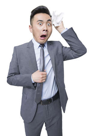 Young businessman wiping sweat with terrified expression