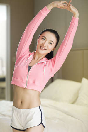 Young woman stretching in bedroom LANG_EVOIMAGES