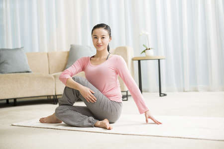 self conscious: Young woman practicing yoga in living room