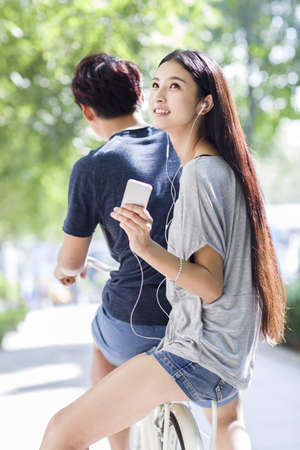 Young woman sitting on boyfriends bicycle and listening to earphones LANG_EVOIMAGES