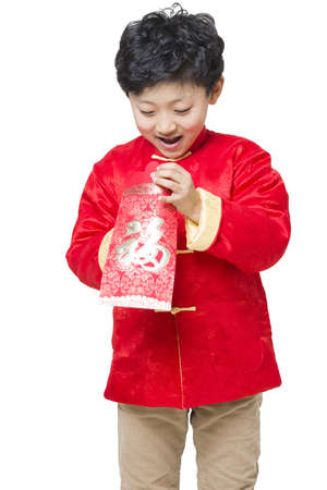 finding out: Surprised boy opening red envelope