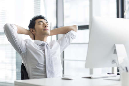 arms behind head: Young businessman resting in office LANG_EVOIMAGES