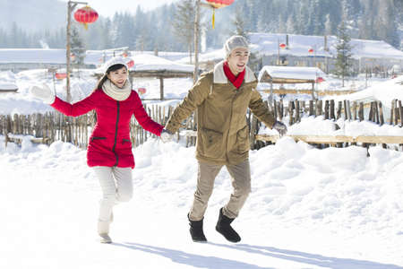 Young couple holding hands running in the snow