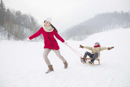 ski walking: Young mother pulling son on sled LANG_EVOIMAGES