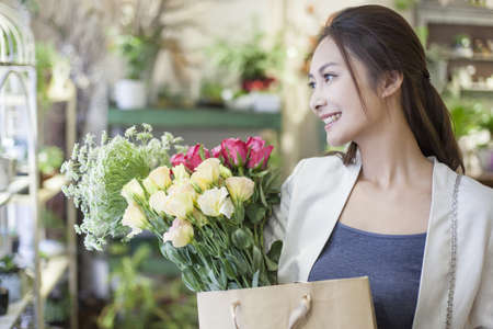 people: Young woman buying flowers