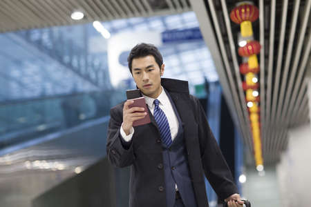 Young businessman walking in airport with passport and smart phone LANG_EVOIMAGES