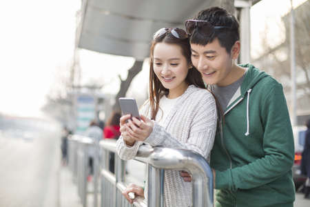 Young couple using smart phone at bus stop