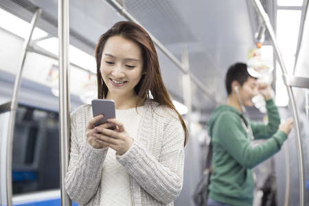 Young woman using smart phone in subway LANG_EVOIMAGES