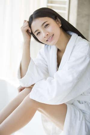 oriental bathrobe: Young woman sitting in bathroom