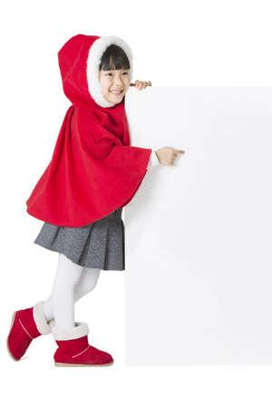 niños vistiendose: Happy girl in Santa suit pointing the blank whiteboard