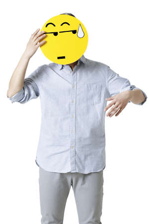 embarrassment: Young man with a embarrassed emoticon face in front of his face