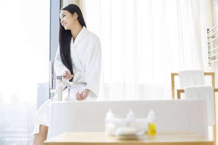 oriental bathrobe: Young woman filling bathtub