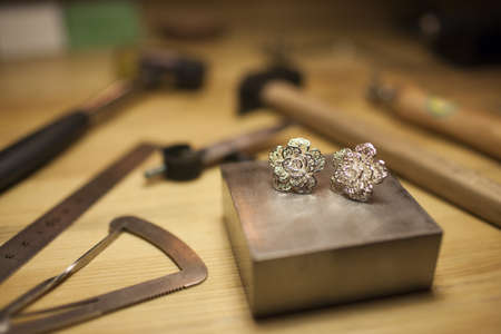 A pair of earrings on jewelers workbench LANG_EVOIMAGES