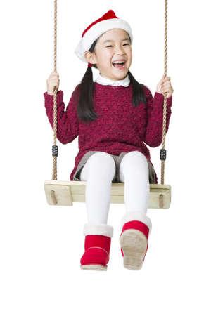 niños vistiendose: Feliz niña en el sombrero de Santa en swing