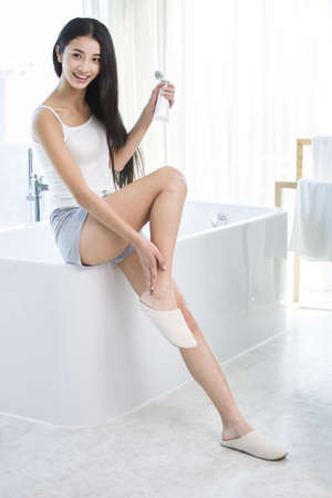 Young woman applying moisturizer to leg LANG_EVOIMAGES