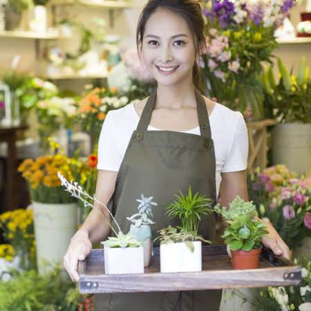 Female florist working in shop LANG_EVOIMAGES