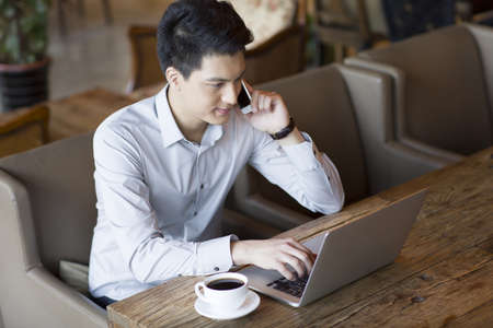 technology: Young man talking on phone and using laptop in cafe
