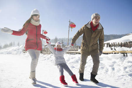 chainlink fence: Happy family playing in the snow