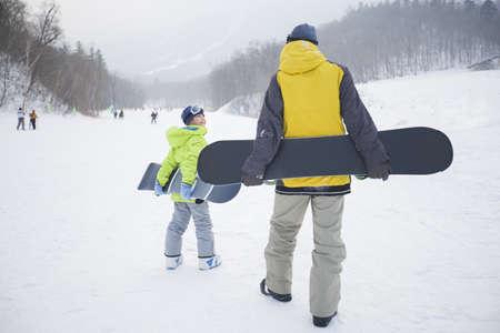 actividades recreativas: Joven padre e hijo caminando con snowboards en la nieve