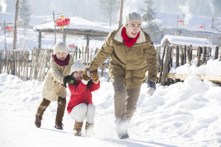 Young father and his children playing in the snow
