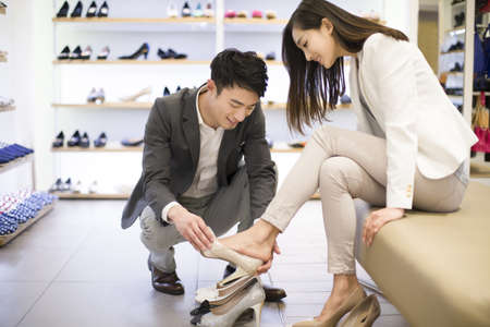 Young couple buying shoes in shop