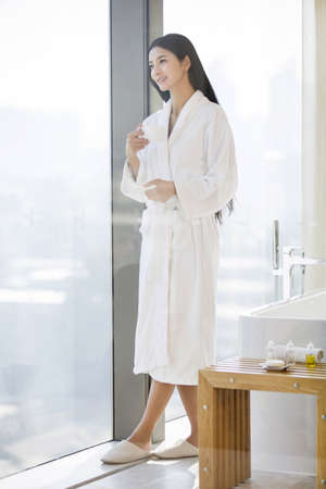 Young woman in bathrobe drinking coffee LANG_EVOIMAGES