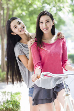 Best female friends riding bicycle at campus
