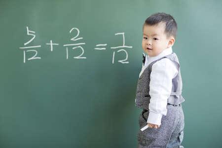 mathematician: Cute baby doing mathematics on blackboard