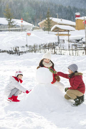 chainlink fence: Happy children making snowman together