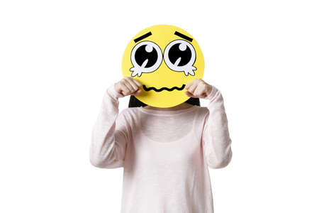 Young woman with a crying emoticon face in front of her face LANG_EVOIMAGES