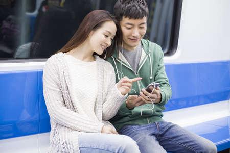 Joven pareja escuchando música en metro LANG_EVOIMAGES