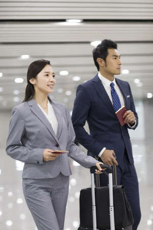Young business person walking in airport with suitcases LANG_EVOIMAGES