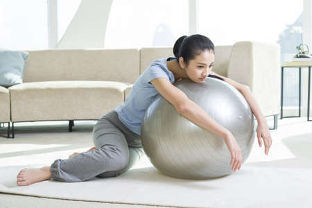 self conscious: Displeased young woman leaning on fitness ball