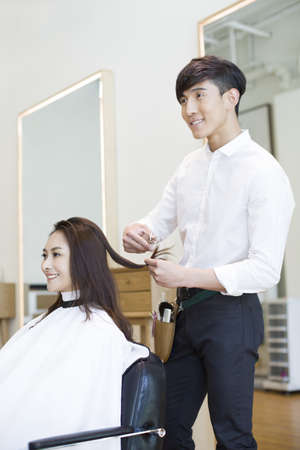 indian style sitting: Barber cutting customers hair