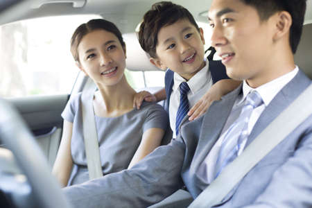 drivers seat: Young couple with son riding in car together