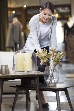 Mature woman arranging flowers in her store